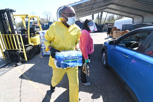 Volunteer Cory Anderson carries cases of bottled water for clients at the Greater Holy Temple in Flint on Thursday, May 7, 2020.