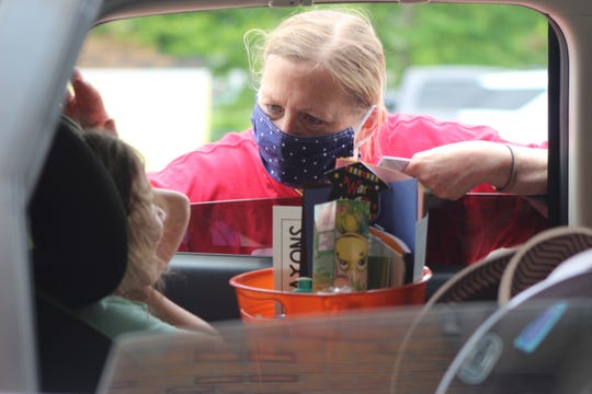 Great Lakes Early Childhood teacher Karen Dorsey speaks to a child during a drive through event on May 29.
