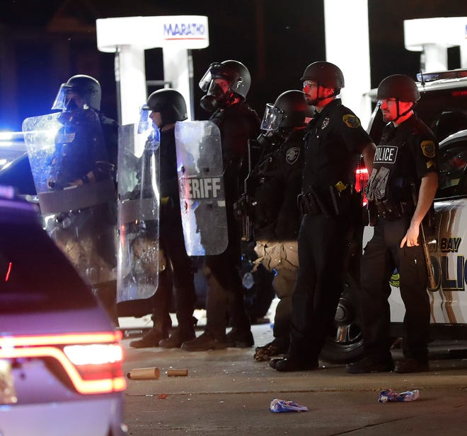 Green Bay police officers stand guard outside the Marathon gas station after some people began throwing objects and attempting to loot the business after midnight on June 1 in downtown Green Bay. The damage followed peaceful protests on May 31.