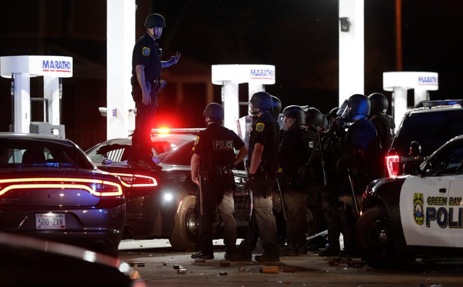 Green Bay police officers listen to instructions at the Marathon gas station on the corner of Walnut Street and Monroe Road during protests downtown after midnight on June 1, 2020, in Green Bay, Wis.
