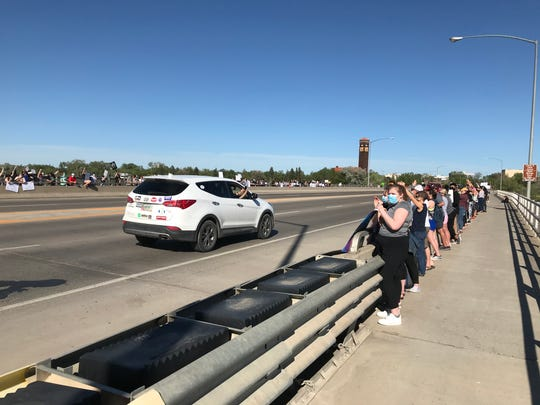 """Residents lined both sides of the Central Avenue West bridge during a rally Sunday in Great Falls. """"This crowd is amazing,"""" said Jasmine Taylor, one of the event's organizers."""