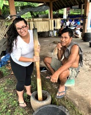 Alyssa Gordon learns from a Balinese man how to use a large mortar and pestle to grind the bark of a tree root to make natural dye for handmade textiles. She spent 12 days in Bali as part of an immersive learning experience for her Community Development class.