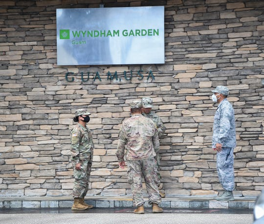 Guam National Guard members gather at the front of the Wyndham Garden Guam on Ypao Road in Tamuning, June 1, 2020. The Guard is assisting in the home transfer for over 100 returning residents undergoing quarantine in a government facility.