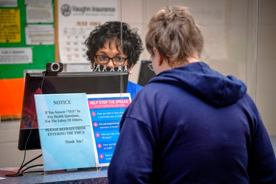 Behind a plexiglass shield. desk clerk Joann Lansden waits while a client reads the medical questionnaire, as the Henderson County YMCA opens with a Phase 1 distancing plan, allowing members access to the fitness centers, cardio and strength areas, with restrictions on capacity and spacing, June 1, 2020.