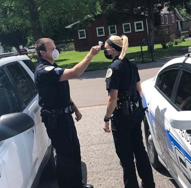 HPD Sgt. Ryan Walenga takes Officer Ellie Steiner's temperature during shift change (May 6, 2020).