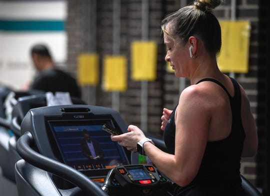 Working out the cardio room, Rachel Banks checks her phone as the Henderson County YMCA opens with a Phase 1 distancing plan, allowing members access to the fitness centers, cardio and strength areas, with restrictions on capacity and spacing, June 1, 2020.