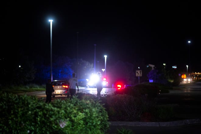 People are illuminated by police lights as enforcement officials respond to a scene of an attempted break in at Coral Ridge Mall, Sunday, May 31, 2020, in Coralville, Iowa.