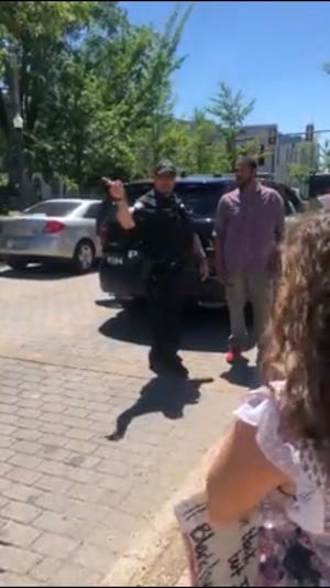 Jackson Police Officer Tommy Ferguson talks with a protester on Main Street in front of City Hall on Saturday just after he'd dropped off a couple of cases of water for the protesters.