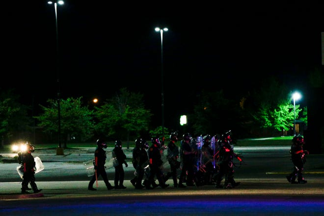 Police officers in riot gear move across the Tippecanoe Mall parking lot to disperse a group of cars parked in the lot following a break in at the Best Buy store, Monday, June 1, 2020 in Lafayette.