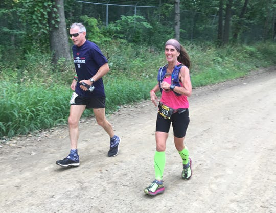 Drew Williams (left) of Colorado Springs and Kris Taubitz of Swartz Creek run on Kelly Road during Run Woodstock in 2018. The trail-racing festival in Pinckney has been canceled for 2020.