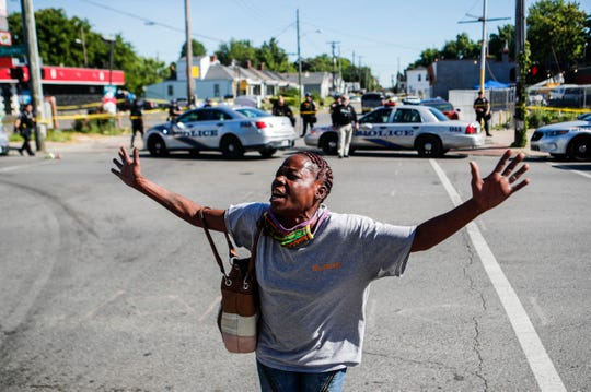 "Louisville, Ky., resident Lenora Moore yells, ""My mouth is a weapon"" at the intersection of 26th and Broadway on June 1 after a man was shot and killed outside Dino's Market."