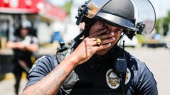 LMPD officer Christian Lewis wipes tears away after hugging a few citizens as hundreds gathered to protest the death of David McAtee, a beloved BBQ owner who shot and killed amid gunfire by LMPD and Kentucky National Guard early Monday morning near 26th and Broadway in West Louisville. June 1, 2020