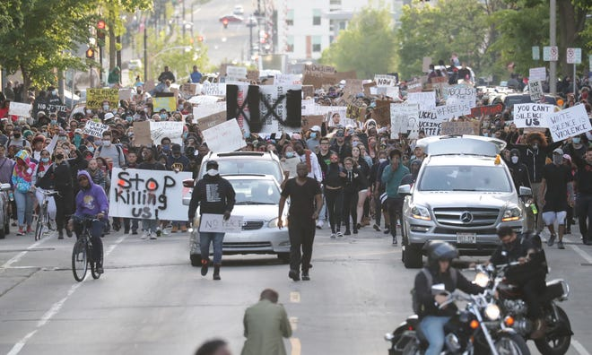 Protesters head down East Juneau Avenue near Jackson Street in Milwaukee on Sunday. The protest was in response to the killing of George Floyd by a Minneapolis police officer.