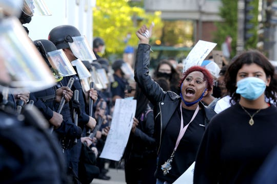 Milwaukee police officers stand guard as protesters make their voices heard in front of the Milwaukee Police Administration Building in Milwaukee on Sunday. The protest was in response to the killing of George Floyd by a Minneapolis police officer.