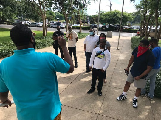 Elijah Brass talks to fellow protesters Monday afternoon outside the Ouachita Parish Courthouse. Residents demanded the resignation of police juror Jack Clampit, District B, because of statements made online over the weekend.
