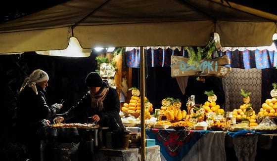 Women sell smoked cheese at the Christmas market in Krakow Poland.