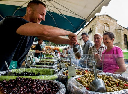 An olive seller at the market in Pertuis, France.