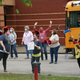 Wearing masks, teachers prepare to greet students.