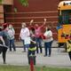 Wearing masks, teachers prepare to greet students.