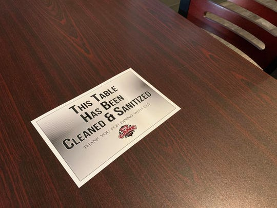 A laminated sign confirms that a table at The Game Sports Bar and Grill on S. Espina Street has been sanitized since its last use. Seen on Monday, June 1, 2020.