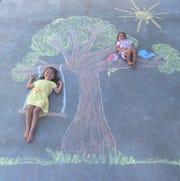 Audrey Ruiz, 4, and Adrianne, 2, pose with chalk art designed by their mother Krystal Ruiz.