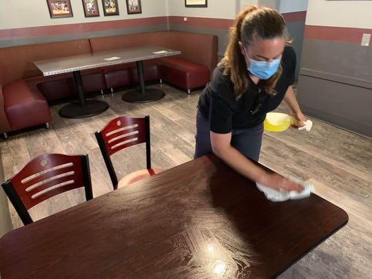 At The Game Sports Bar and Grill on S. Espina Street, owner Marci Dickerson demonstrates how tables, chairs and booths at the restaurant will be sanitized between every use on the day New Mexico restaurants were allowed to reopen for limited dine-in service during the COVID-19 emergency, Monday, June 1, 2020.
