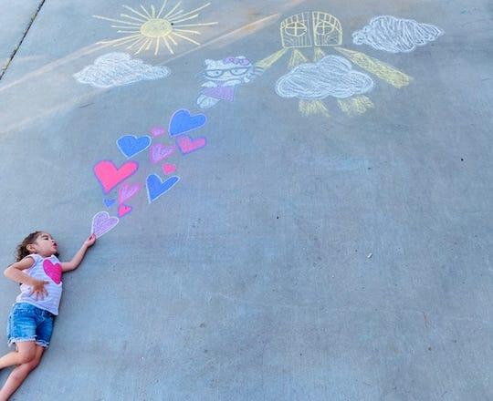 Adrianne Ruiz, 2, poses with chalk art designed by her mother Krystal Ruiz.