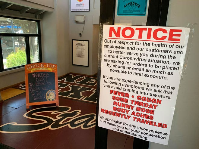 At the entrance to The Game Sports Bar and Grill on S. Espina Street, customers are greeted on Monday, June 1, 2020 by two signs: One welcoming them back after several weeks of COVID-19 restrictions, and another asking them to stay away if they have symptoms or have recently traveled outside New Mexico.