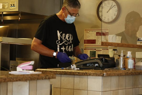 Chris Cerny of the Pecos Valley Cafe in Carlsbad completes a transaction on June 1, 2020. As required by state emergency health laws restaurants can open at 50 percent capacity and must still maintain at least 6 feet of distance.