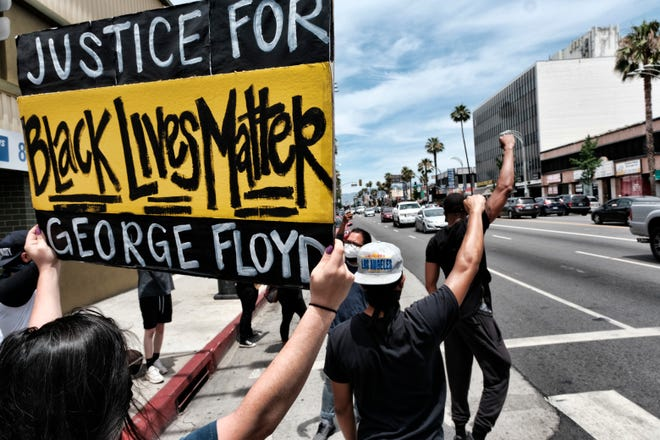 Protesters hold up signs and raise their fists as traffic passes on a street corner in the Van Nuys section of Los Angeles on Monday, June 1, 2020, over the death of George Floyd, a black man who was in police custody in Minneapolis. Floyd died after being restrained by Minneapolis police officers on Memorial Day.