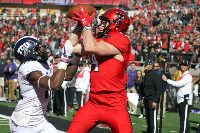 Texas Tech Red Raiders wide receiver Dylan Cantrell (14) attempts to catch a pass in front of TCU Horned Frogs defensive back Jeff Gladney (12) at Jones AT&T Stadium.