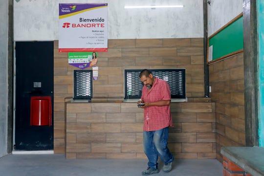 Fotografía del 7 de febrero de 2020 que muestra a un hombre que retira dinero en una casa de cambio de divisas en el municipio de Tepeojuma.