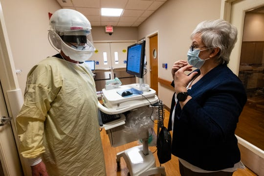 Denise Parr, Lake Huron Medical Center's infection prevention specialist, right, instructs Respiratory Therapist Larry Winter on the proper way to remove his PPE after working with a patient Friday, May 15, 2020, in the hospital's emergency department.