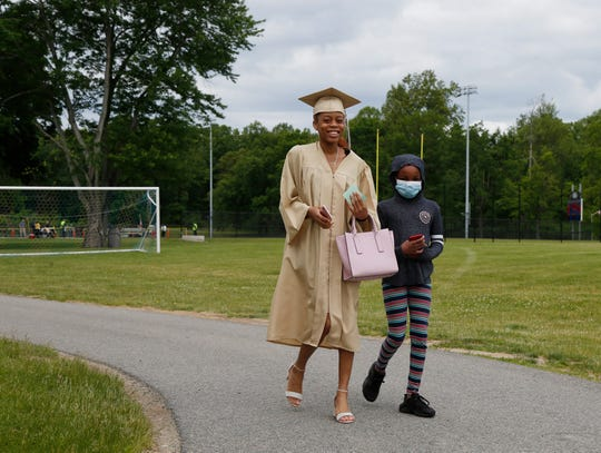 Nyeema McGawn walks with her sister Chelsea Gordon after walking across the stage for the graduation celebratory walk at Beacon High School on June 1, 2020.