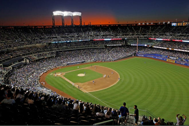 In this Aug. 29, 2019, file photo, the sun sets behind Citi Field during a baseball game between the New York Mets and the Chicago Cubs in New York. Major League Baseball players and owners are in labor stalemate.