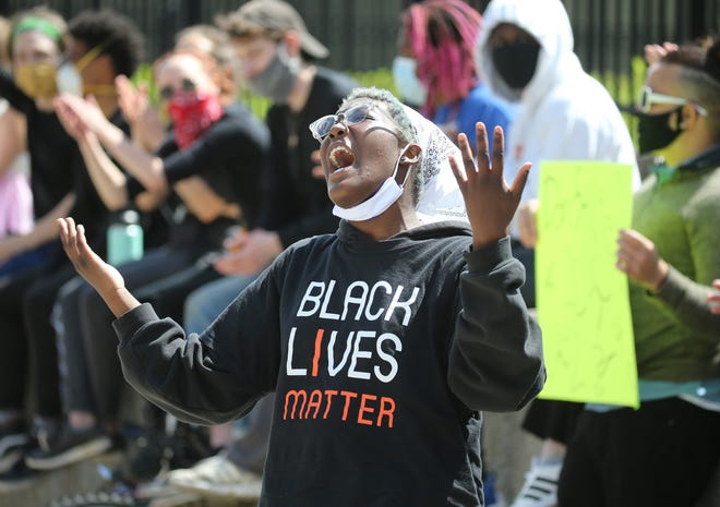 Protesters chant against police bias against minorities during a rally Monday outside the Hall of Justice.