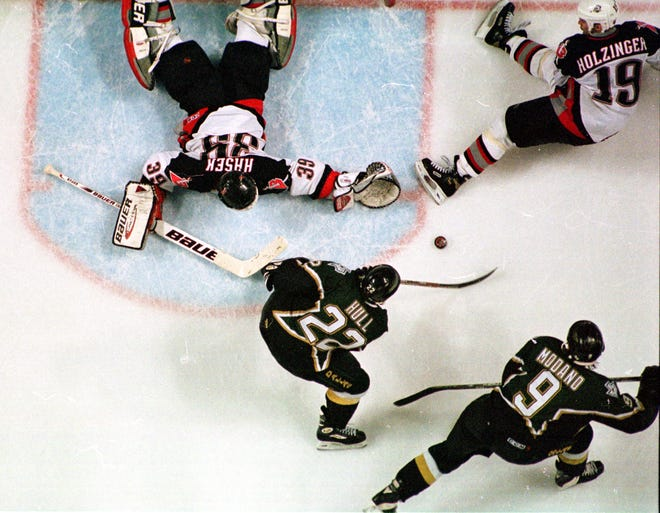 With one skate in the crease, Dallas' Brett Hull shoots the Stanley Cup-winning goal past sprawling Buffalo Sabres goalie Dominik Hasek.