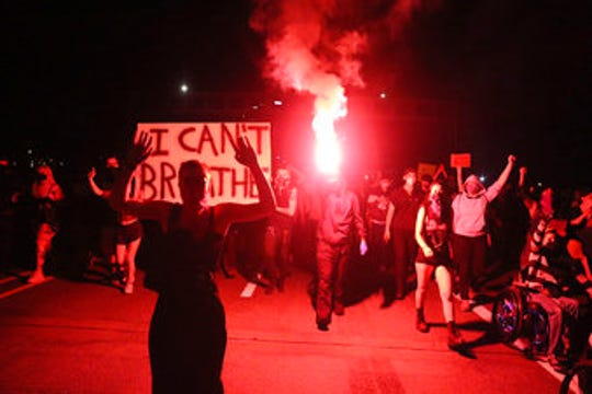 In this May 29, 2020, photo, Portlanders march with flares from the George Floyd vigil at Peninsula Park toward the Justice Center downtown in Portland, Oregon.