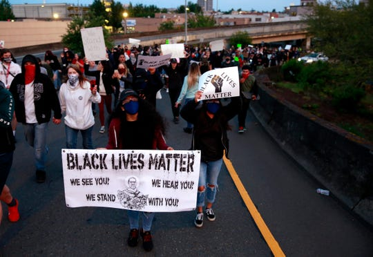 Protesters march up a ramp onto the Marion Street Bridge in Salem, Oregon, on Sunday, May 31, 2020. They were protesting the death of George Floyd, who died in police custody on May 25 in Minneapolis.