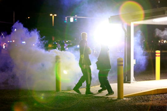 Police officers fire tear gas and use a high-powered spotlight to disperse demonstrators during a protest in Salem, Oregon, on Sunday, May 31, 2020.
