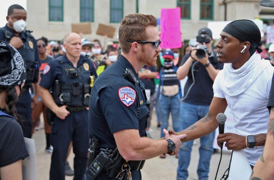 A protestor shakes hands with a police officer near the steps of city hall in San Angelo on Sunday, May 31, 2020.