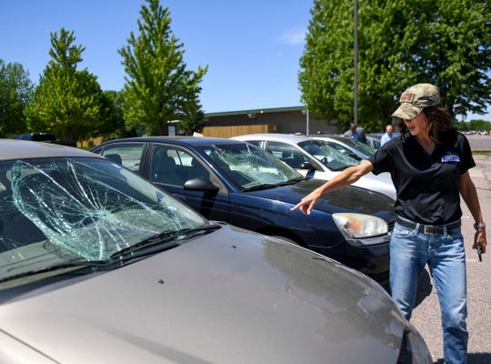 Gov. Kristi Noem surveys the damage done to vehicles after Sunday's protests turned violent on Monday, June 1, 2020 at the School for the Deaf in Sioux Falls, S.D.