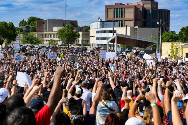Hundreds of protestors hold up the black power symbol with their fists in the air to demand justice for George Floyd, joining nationwide protests on Sunday, May 31, in Sioux Falls.
