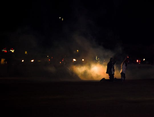 Two protesters kneel in a cloud of tear gas on Sunday, May 31, 2020 in Sioux Falls, S.D.