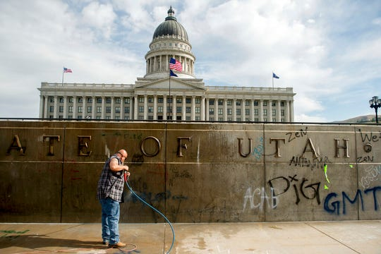 Don Gamble cleans up graffiti at the Capitol in Salt Lake City on Sunday, May 31, 2020, following protests over the death of George Floyd. Protests were held throughout the country over the death of Floyd, a black man who died after being restrained by Minneapolis police officers on May 25.   (Jeremy Harmon/The Salt Lake Tribune via AP)