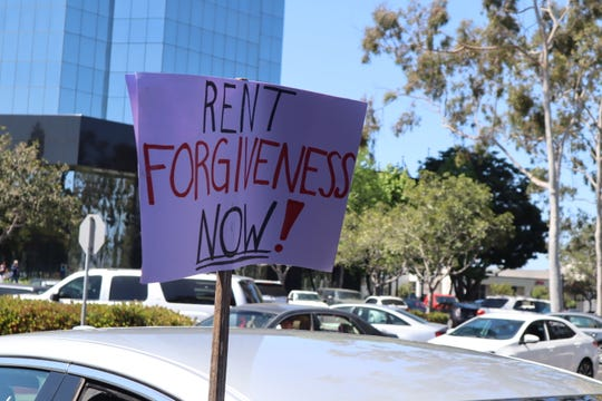 A sign calls for rent forgiveness at CAUSE's May Day car caravan on May 1. The event called on legislators to support the working class and cancel rent.