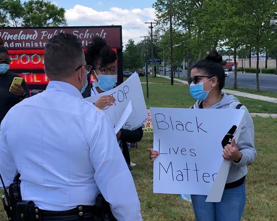 Protesters Tahira Davis (left) and Mia Arbona, speak with Acting Vineland Police Chief Pedro Casiano before their peaceful march to demand justice for George Floyd, the black Minneapolis man who died in police custody. Casiano and other police officers walked alongside the protesters during the march.  June 1, 2020