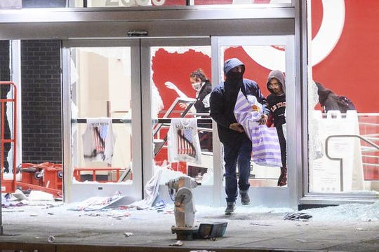 People leave a vandalized Target store in Oakland, Calif., on Saturday, May 30, 2020, during protests against the death of George Floyd, a handcuffed black man in police custody in Minneapolis. (AP Photo/Noah Berger)