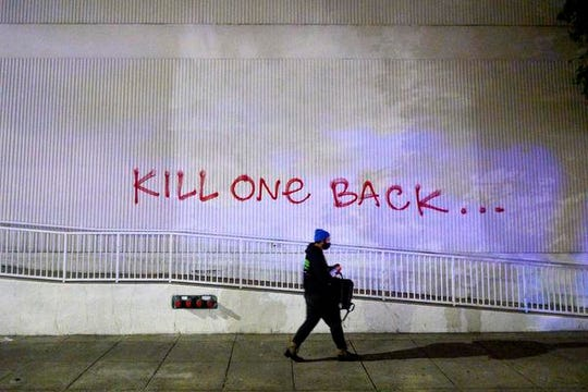 A demonstrator passes graffiti in Oakland, Calif., on Friday, May 29, 2020, while protesting the Monday death of George Floyd, a handcuffed black man in police custody in Minneapolis. (AP Photo/Noah Berger)