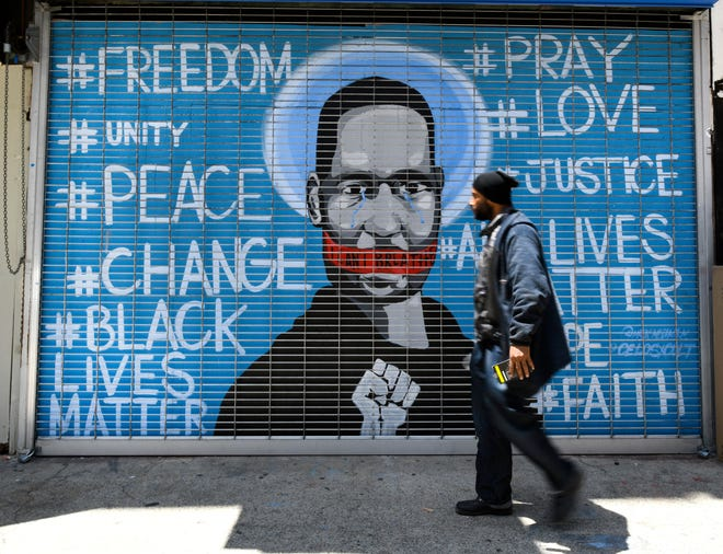 A man walks past a protest mural on a closed business on in Los Angeles.